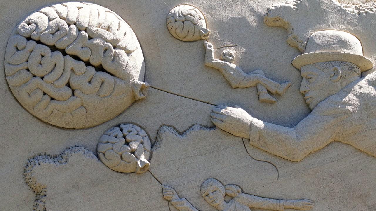Gehirnballons aus Sand geformt, die Menschen nach oben ziehen